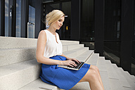 Blond businesswoman sitting on stairs using laptop - GDF01123