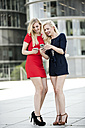 Two fashionable women looking at their smartphones - GDF01144