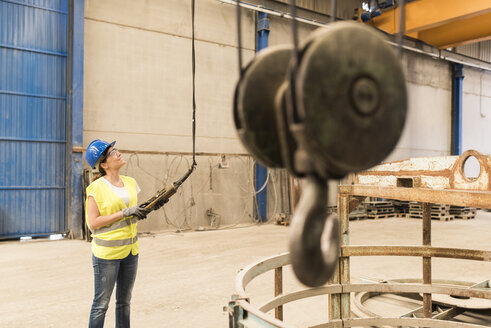Woman using control in factory hall - JASF01151