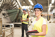Portrait of smiling woman in factory hall - JASF01157