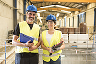 Portrait of two smiling colleagues in factory hall - JASF01160