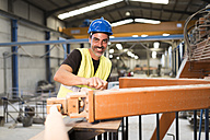 Worker in a factory adjusting girder - JASF01166