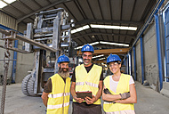 Portrait of three smiling colleagues in factory hall - JASF01169
