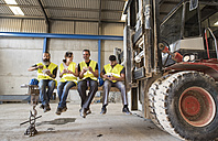Workers having lunch on the shovel of a giant forklift - JASF01172