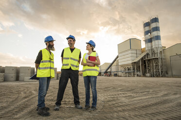 Three people in safety vests on industrial site - JASF01196