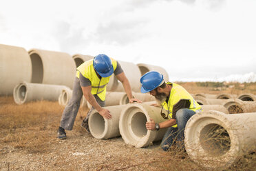 Industrial workers examining concrete pipes - JASF01205