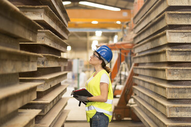 Woman looking at material in factory hall - JASF01217