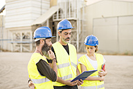 Three people in safety vests on industrial site - JASF01232