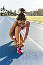 Female athlete tying shoes on race track - MGOF02484