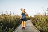 Happy little girl jumping on boardwalk in nature - JRFF00867
