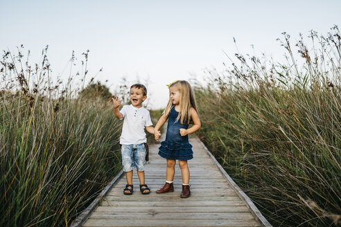Two little children playing together on boardwalk in nature - JRFF00873