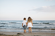 Back view of little boy and girl standing side by side at seashore - JRFF00882