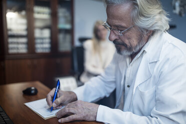 Ophtalmologist writing medical record of patient - ZEF10559