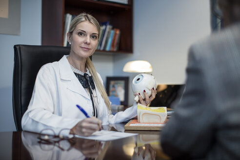 Female optometrist talking to patient, holding model of eyball - ZEF10577