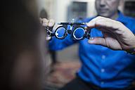 Optometrist holding test frames for girl - ZEF10586