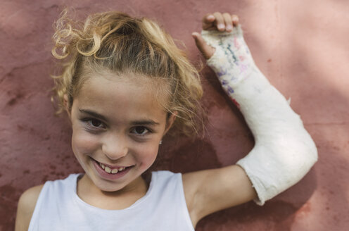 Portrait of smiling blond girl with plastered arm - RAEF01504
