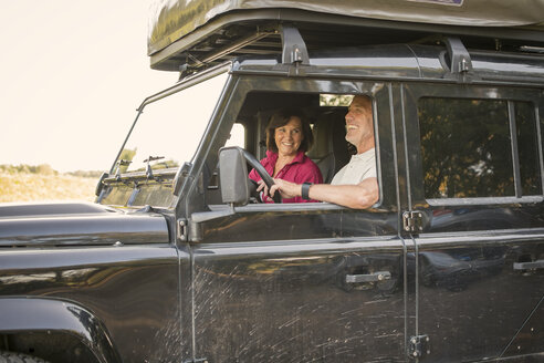 Happy senior couple on a trip in a cross country vehicle - ONF01015