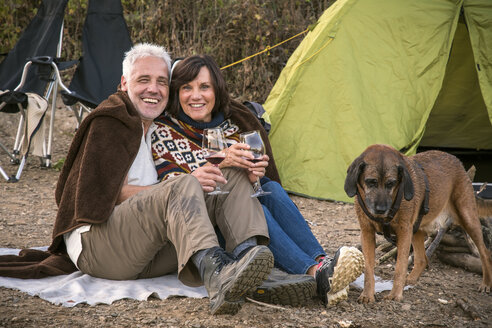 Happy senior couple with wine and dog at a tent - ONF01039