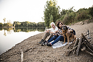 Happy senior couple with dog at a lake in the evening - ONF01042