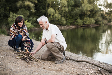 Senior couple lighting a campfire at a lake in the evening - ONF01045