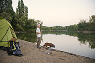 Senior man with dog camping at a lake - ONF01051