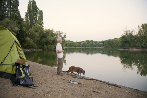Senior man with dog camping at a lake - ONF01051