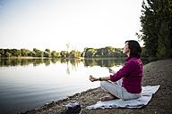 Senior woman at a lake practicing yoga - ONF01069