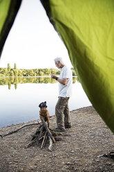 Senior man with dog camping at a lake - ONF01075