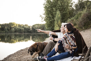 Senior couple with dog at a lake in the evening - ONF01081