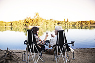Senior couple clinking wine glasses at a lake in the evening - ONF01084