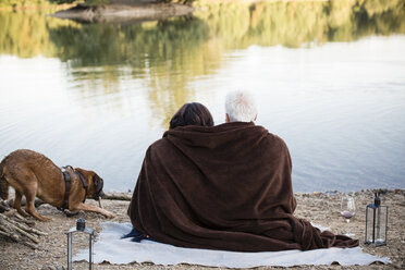 Relaxed senior couple with dog at a lake - ONF01090