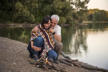 Senior couple at campfire at a lake - ONF01093