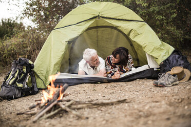 Happy senior couple lying in tent at campfire - ONF01102