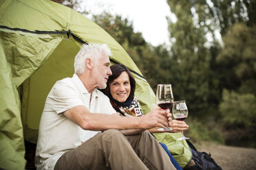 Senior couple sitting with wine in a tent - ONF01105