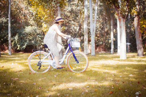 Woman riding bicycle in autumnal park - JPSF00016