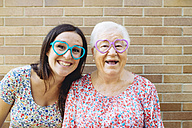 Happy granddaughter and grandmother wearing heart-shaped glasses - GEMF01122