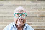 Portrait of senior man wearing heart-shaped glasses pulling funny faces - GEMF01125