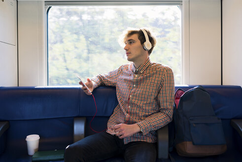 Young man sitting in a train listening music with headphones - FMOF00130