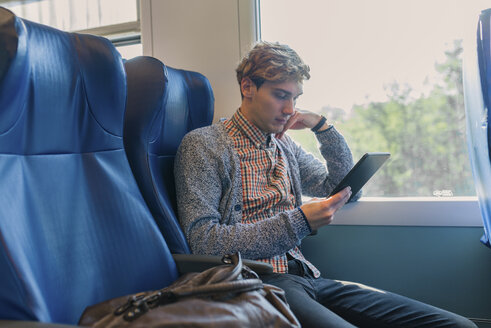 Young man sitting in a train looking at tablet - FMOF00133