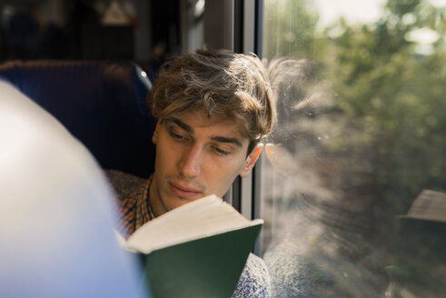 Young man reading book in a train - FMOF00136