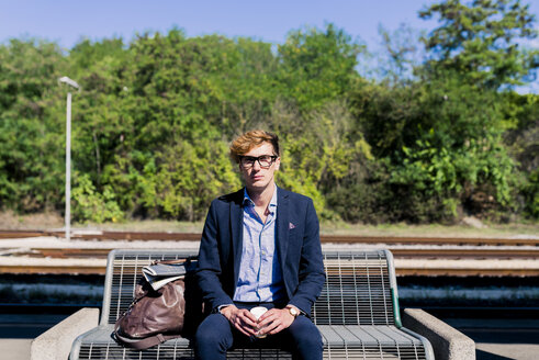 Young businessman with coffee to go sitting on bench at platform - FMOF00142