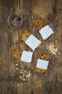 Homemade granola bars and a glass of honey on wood - LVF05400