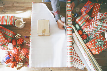Woman cutting wrapping paper for Christmas gifts - RTBF00425