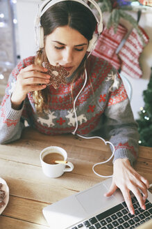 Woman with headphones using laptop while eating Christmas cookie - RTBF00431
