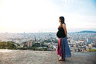 Spain, Barcelona, Pregnant woman enjoying view over city - GEMF01128