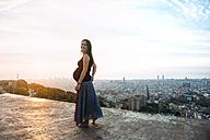 Spain, Barcelona, Pregnant woman enjoying view over city - GEMF01131