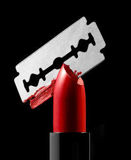 Razor blade cutting through red lipstick - RAMF00067