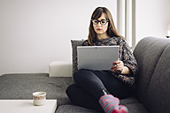 Young woman sitting on the couch using her tablet - LCUF00047