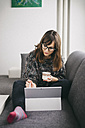 Young woman sitting on the couch with cup of coffee drawing on her tablet - LCUF00050
