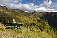 Austria, Carinthia, Drau Valley, woman sitting on bench in mountain landscape - GFF00790